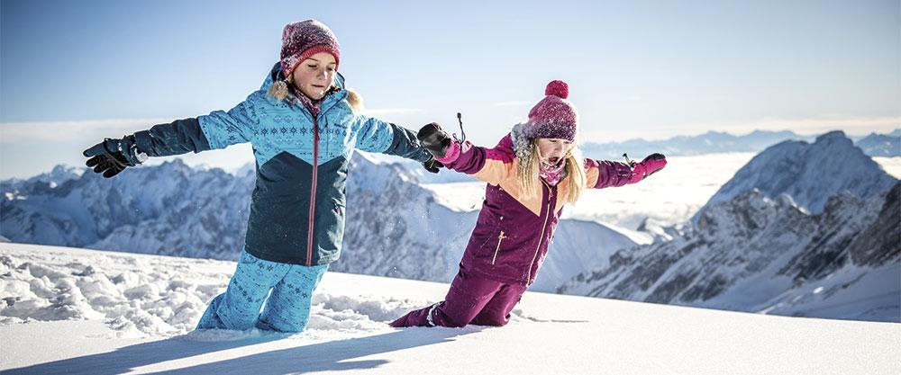 begeisterte Kinder mit Ziener Ski-Kleidern